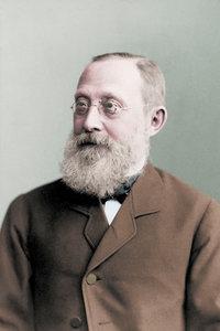 Ein koloriertes Foto aus dem Jahr 1887 zeigt den Mediziner und Reichstagsabgeordneten Rudolf Virchow. Er trägt einen dichten grauen Bart und eine Brille mit runden Gläsern. Bekleidet ist er unter anderem mit einer braunen Anzugjacke.