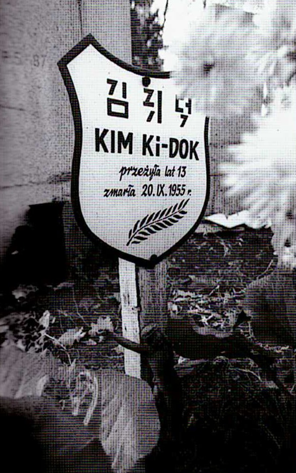 Plaque funéraire de Kim Ki-dok. Il est écrit : « 김키덕 / Kim Ki-DOK / elle a vécu 13 ans / elle est morte le 20.IX.1955 » (le deuxième syllabogramme coréen est peu lisible), Cimetière Osobowice, Wrocław (les orphelins nord coréen)