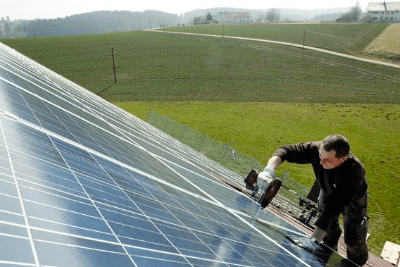 Worker installing solar panels on a barn in Binsham, Germany (Source: Creative Commons)
