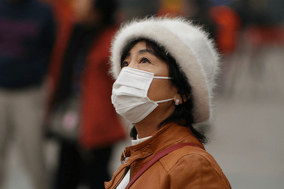 A Chinese woman wearing a surgical mask outside. (Image Credit: Nicolò Lazzati)