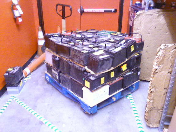 A pallet of scrap lead-acid automotive batteries being collected for recycling. (Image Credit: WikiMedia Commons)