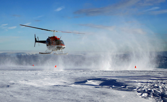A helicopter is taking off from the Greenland Ice Sheet. (Photo Credit: Brocken Inaglory)