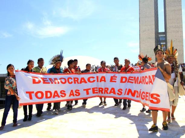 Members of Brazil's indigenous movement occupy the roof of Congress in Brasilia during the annual Terra Livre mobilization. Their banner reads Democracy and Demarcation on All Indigenous Lands. (Photo Credit: CIMI)