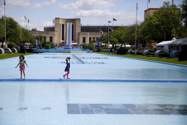 Young girls crossing the narrow bridge that spans the Esplanade fountain in Dallas Fair Park. (Photo Credit: Rick Baraff)