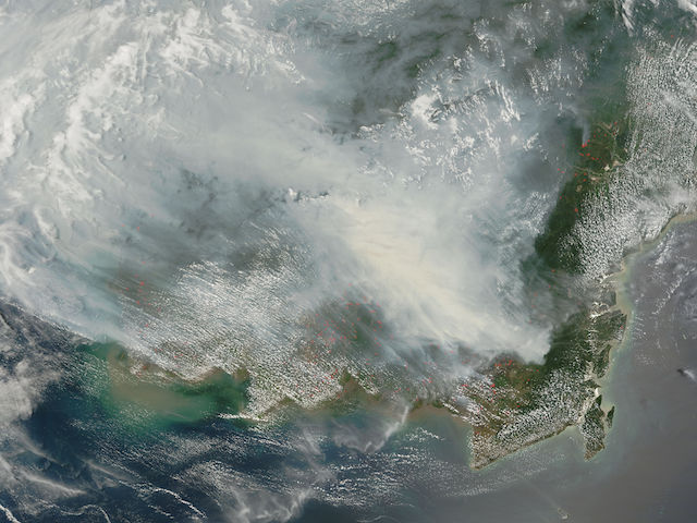 NASA's Terra satellite shows thick smoke over the island of Borneo on 5 October 2006. Fires occur annually in the dry season (August–October), caused mainly by land-clearing and other agricultural fires. (Photo Credit: NASA / Jeff Schmaltz, MODIS Rapid Response Team)