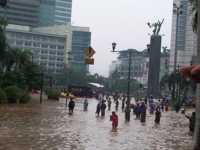 People walk through Jakarta's flooded streets, Indonesia, January 17, 2013. (Photo Credit: VOA Indonesian Service via WikiMedia Commons)