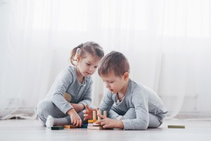 children playing with a wooden toy puzzle
