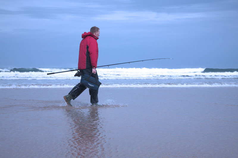 an angler walking alon a surf beach