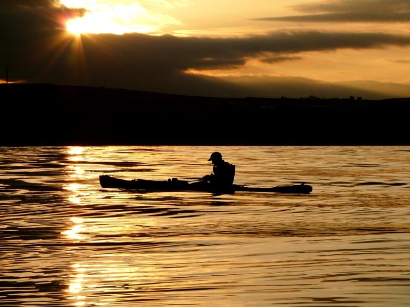 a kayak angler on calm seas at sunset