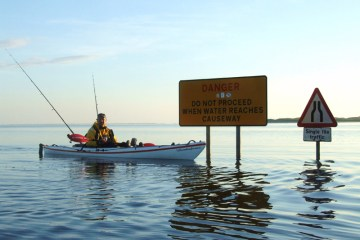kayak besie flooded road signs