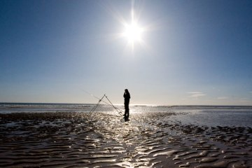 angler standing at rod rest on Elliot beach