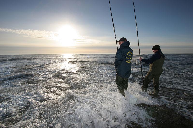 two anglers on an exposed rocky shoreline