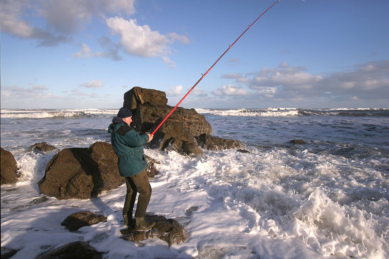 an angler on an exposed wave hit shoreline