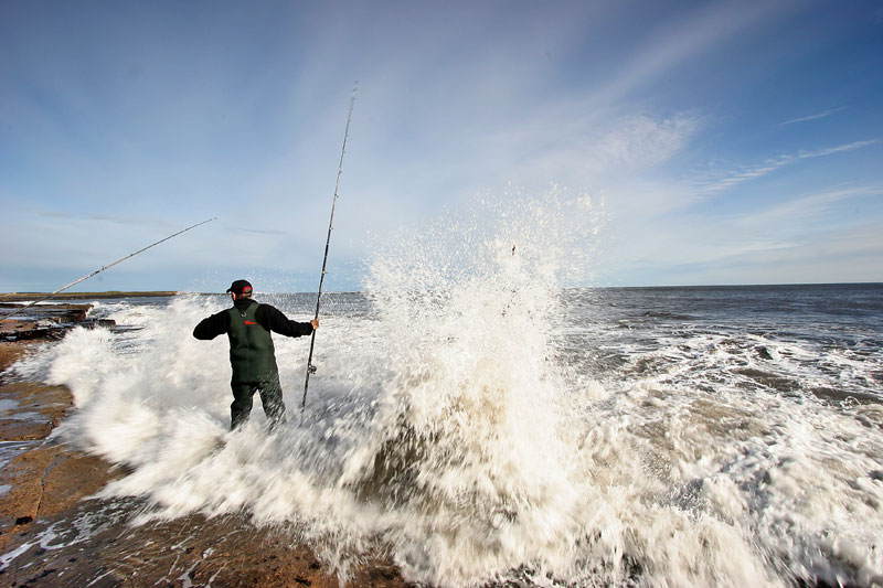 an angler caught on rocks by a breaking wave