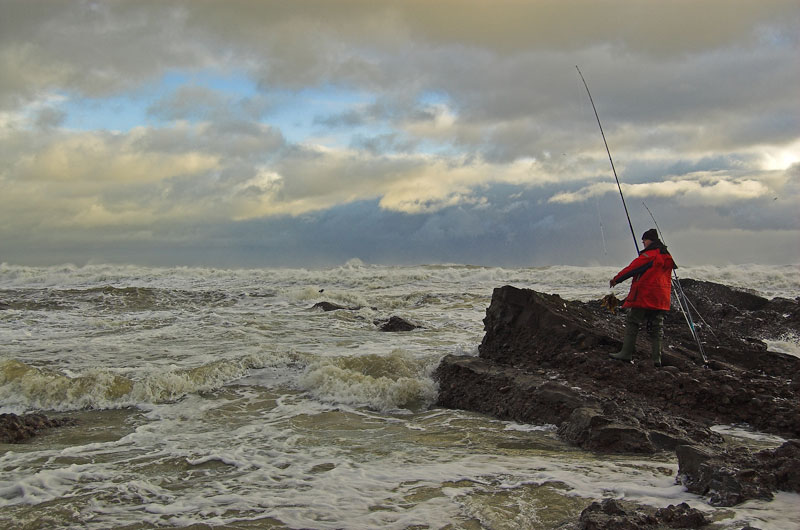 an angler on a rocky shore with churning seas