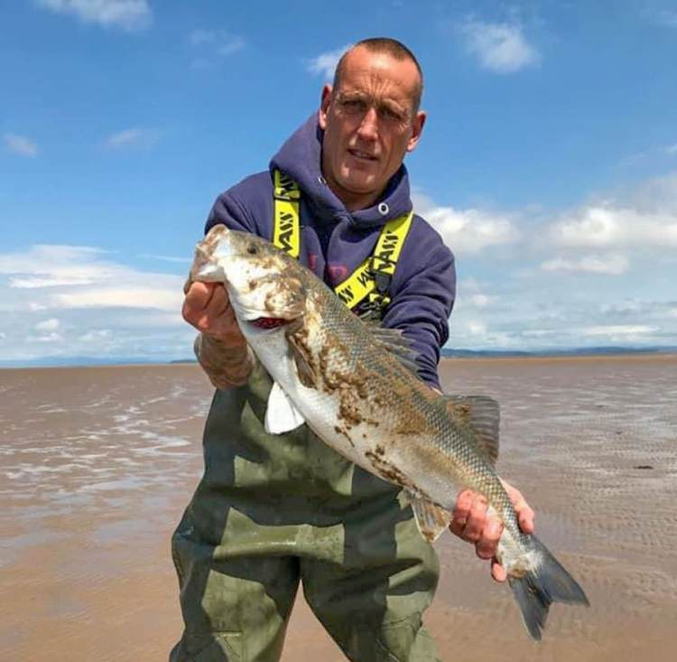 Keith Oldcorn with a cracking bass he caught at low water