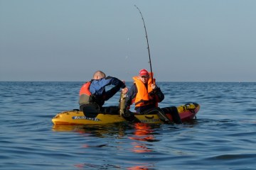 two anglers aboard a kayak land a fish