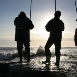 anglers on an exposed rocky shoreline in silhouette