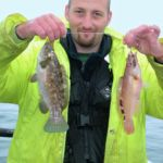 an angler with a ballan wrasse and female cuckoo wrasse double