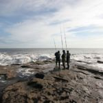 three anglers on an exposed rocky shoreline
