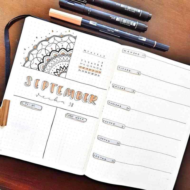 Bullet journal weekly spread for September, with a mandala doodle and on a wood background with pens.