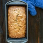 Vegan zucchini bread in loaf pan with blue oven mitt.