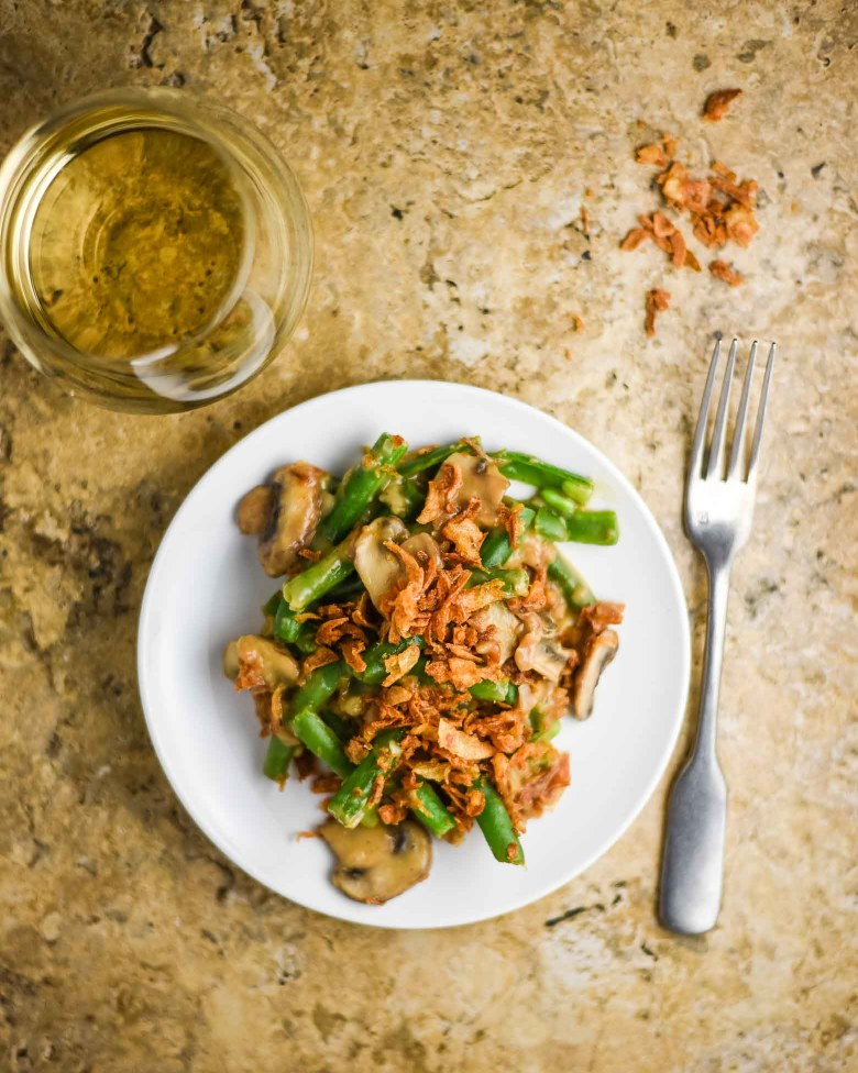 Vegan green bean casserole on a white plate with a glass of white wine.