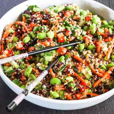 Quinoa edamame salad in a white bowl with a pair of chopsticks