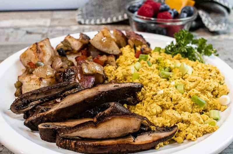 crispy potatoes, scrambled tofu eggs, sliced portobello steaks on a white plate next to a small cup of fresh fruit.