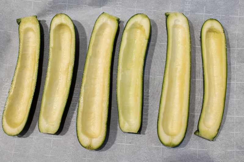 Zucchini cut in half and seeds scooped out on a parchment lined cookie sheet.