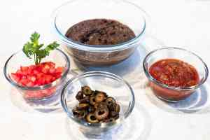dishes of refried beans, chopped tomatoes, olives and salsa