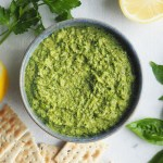 vegan pea pesto in a bowl with lemon herbs and crackers