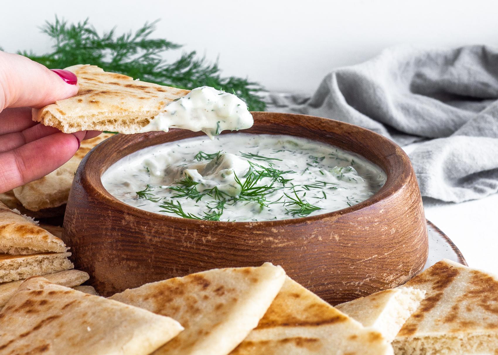 vegan tzatziki in wood bowl with hand dipping pita bread