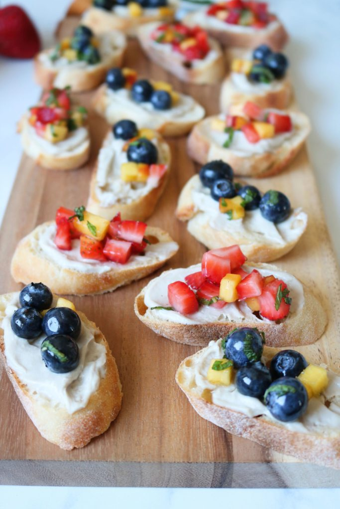 strawberry and blueberry covered Vegan Fruit Bruschetta on a serving tray