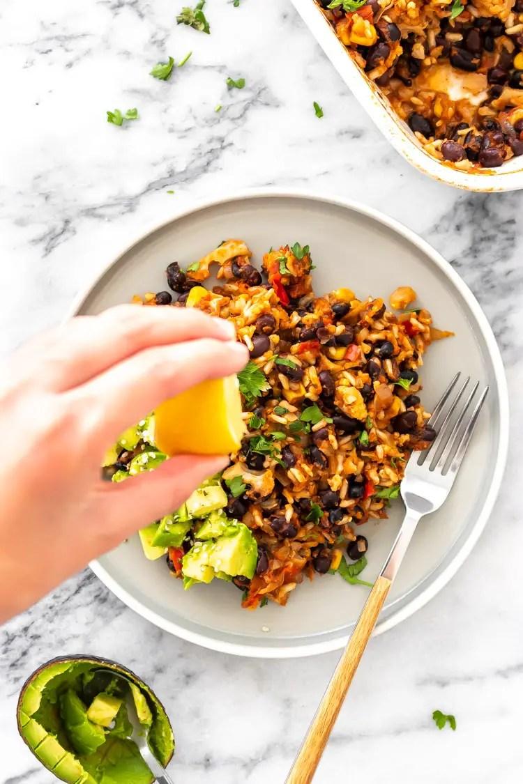 arroz de forno com feijão e vegetais servido no prato com abacate e salsinha