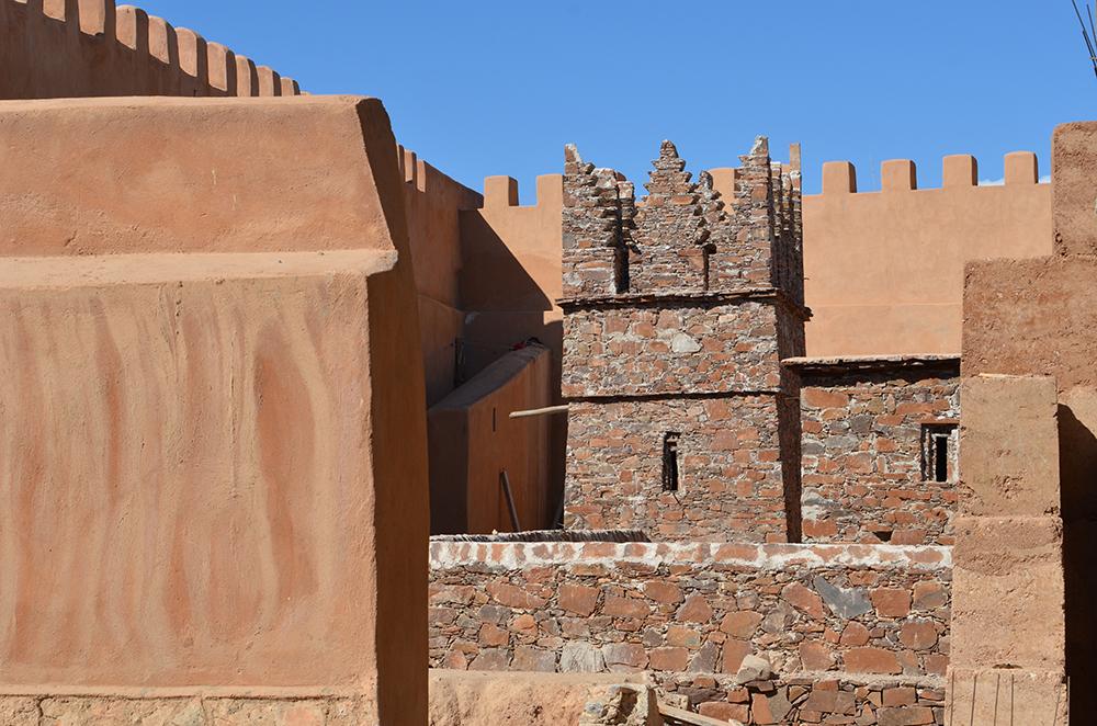 Figure 18 : Vue extérieure du bâtiment dans les remparts de la Kasbah Aghenaj, le grenier en pierre de Wijjane est en cours de construction à l'échelle 1 dans les espaces musographiques, tandis que sont édifiés les murs de pisé sur une structure en Béton armé imposée par la législation. Photos en haut, Mehdi Bensid ©, en bas, Aissam Haddioui ©.