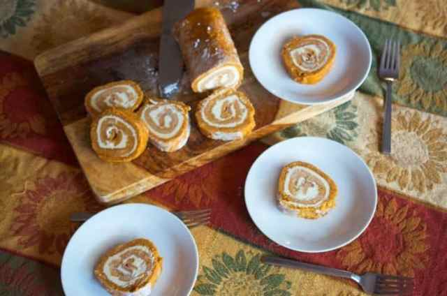Pumpkin roll cake on a cutting board and three white plates holiding slices of pumpkin cake.