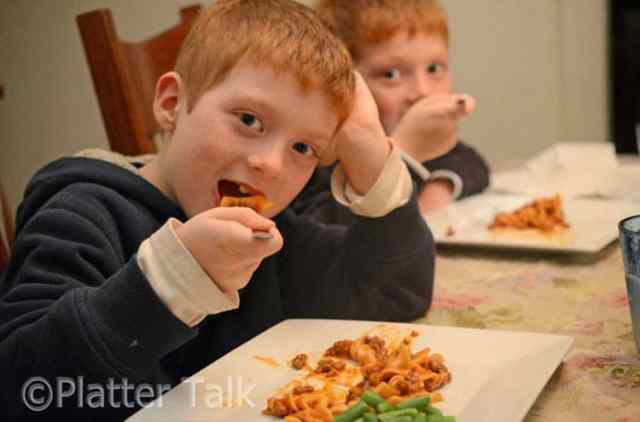Two boys eating beefaroni for dinner.
