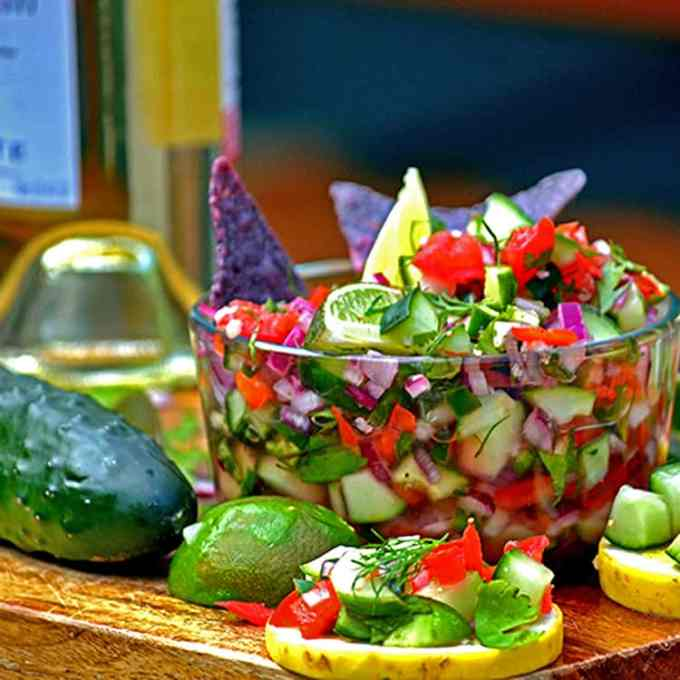 cucumber salsa in a bowl with lime and chips.