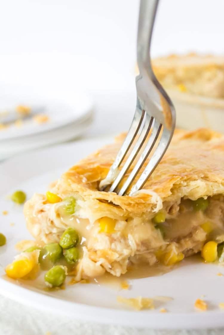 table fork entering a slice of turkey pot pie.