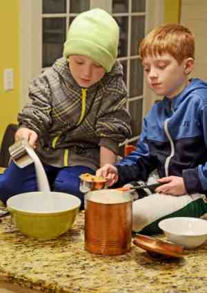 Two young boys making an easy cookie recipe with sugar and peanut butter.