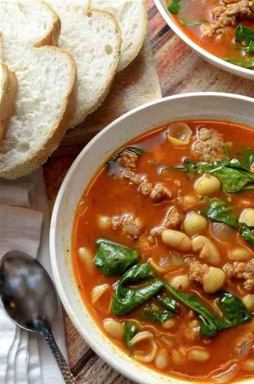 Bowl of white bean soup that uses Italian sausage.