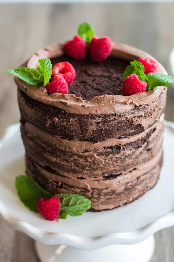 Chocolate keto cake with raspberries and mint leaves.