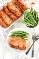 Platter of metloaf cut into portions with green beans on the side.