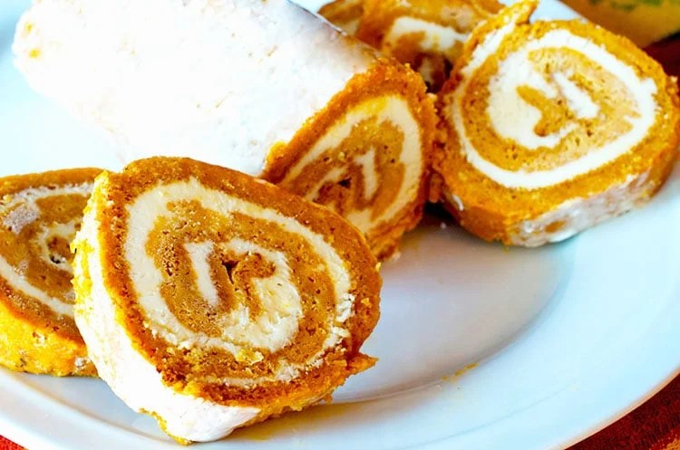Pumpkin roll on a white seviong platter with four slices carved.