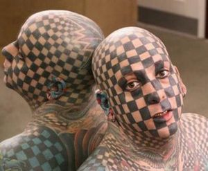 man with checkerboard face tattoo