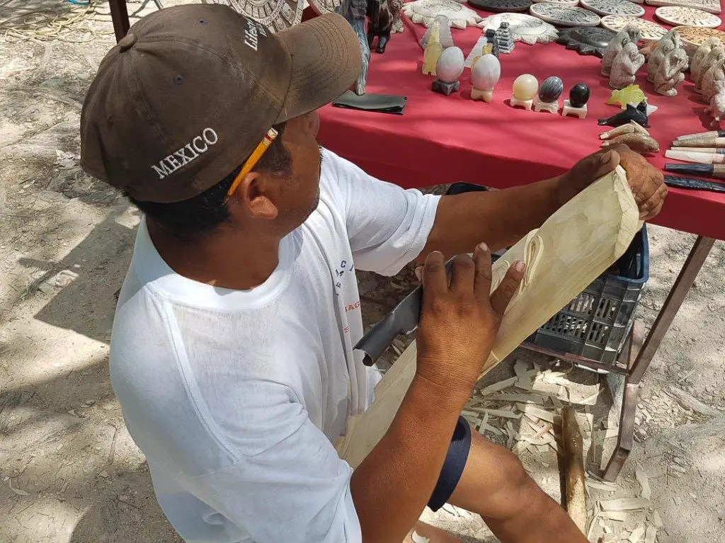 A local resident carves a wooden mask
