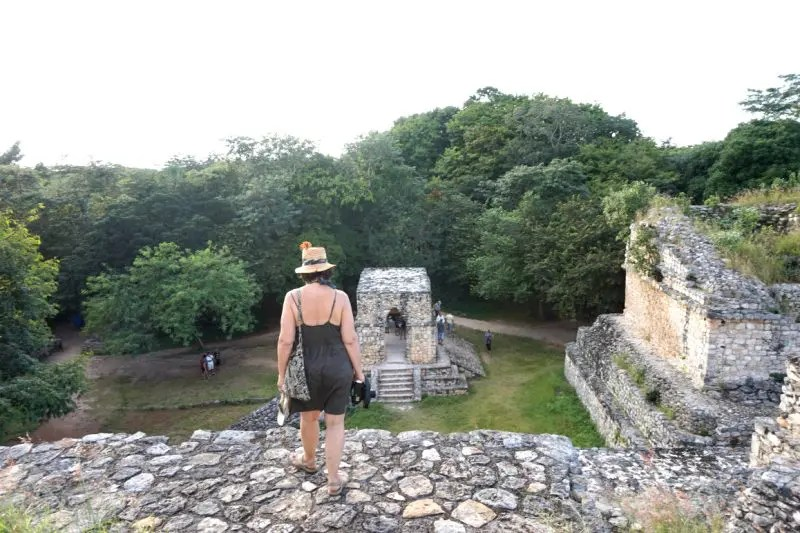 A tourist looks out at the Ek Balam Mayan ruins from atop a pyramid