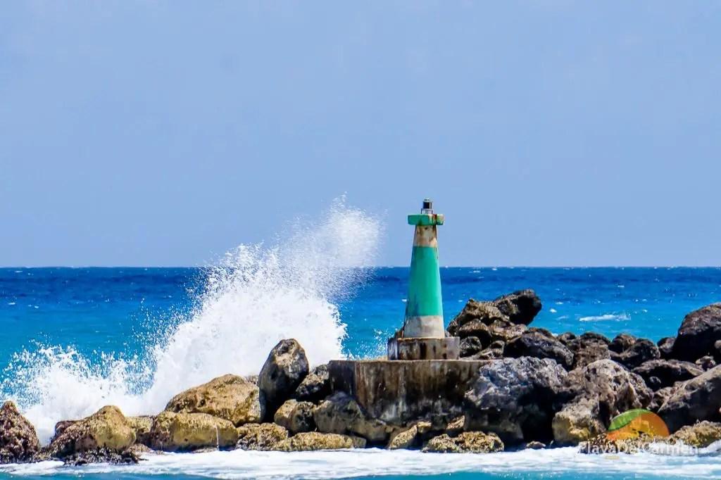 Waves crashing against the min-light tower in Puerto Aventuras