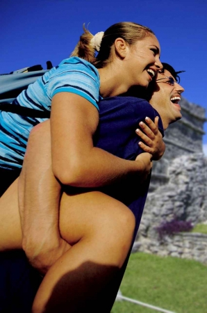 A man carrying a woman piggyback style at a romantic Mayan ruins site.